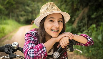 Young girl on bike wearing braces