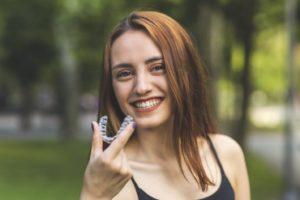 Smiling woman holding aligner during her Invisalign timeline