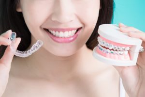 Woman with straight teeth comparing Invisalign vs. braces